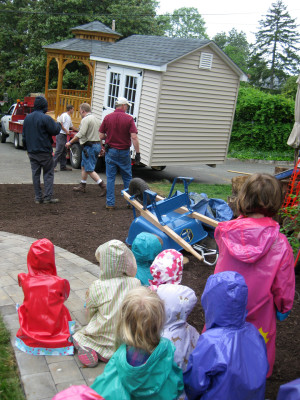 The children watch as the shed and the gazebo are delivered.