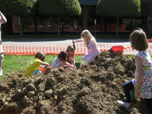 The children watched a dump truck deposit dirt for the construction of the hill. They helped move the dirt to the spot designated for the hill.