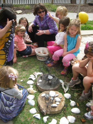 A meeting around a fairy house built in April to lure the fairies to the Outdoor Classroom